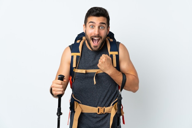勝利を祝う白い壁に分離された大きなバックパックとトレッキングポールを持つ若い登山家の男