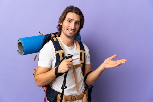 큰 배낭이 와서 초대하기 위해 손을 옆으로 뻗는 젊은 등산가 남자