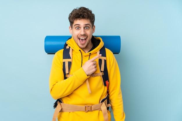 Молодой альпинист с большим рюкзаком изолирован на синем указательном пальце в сторону