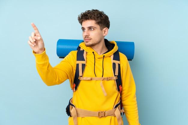 Молодой человек альпиниста с большим рюкзаком, изолированным на синей стене, касающейся прозрачного экрана