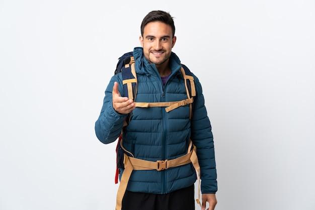 Молодой альпинист с большим рюкзаком изолирован на белой стене рукопожатие после хорошей сделки