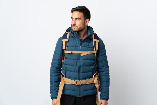 Молодой альпинист с большим рюкзаком на белой стене смотрит в сторону
