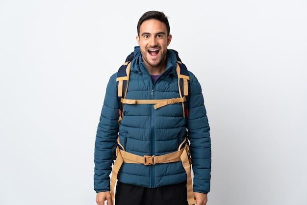 Молодой альпинист с большим рюкзаком изолирован на белой стене с удивленным выражением лица