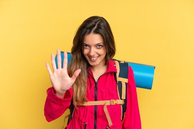 指で5を数える黄色の背景に分離された大きなバックパックを持つ若い登山家の男