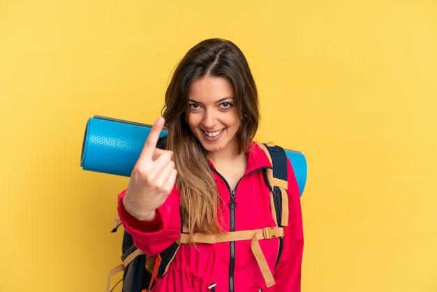 Молодой альпинист с большим рюкзаком на желтом фоне делает приближающийся жест