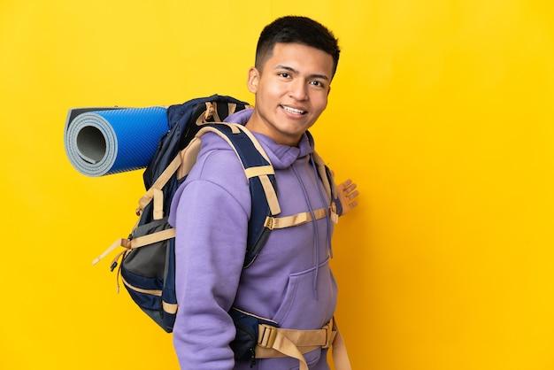 노란색 배경에 고립 된 큰 배낭을 가진 젊은 산악인 남자가 와서 초대하기 위해 손을 옆으로 확장