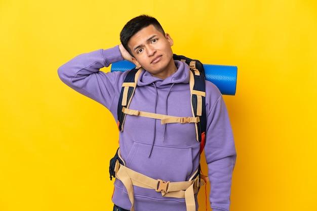 Молодой альпинист с большим рюкзаком на желтом фоне с сомнениями