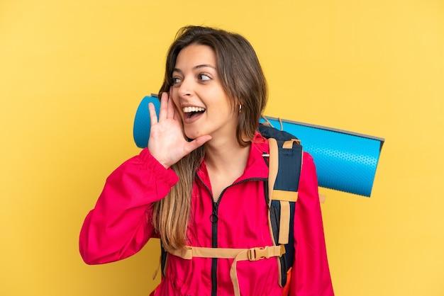 耳に手を置いて何かを聞いて黄色の背景に分離された大きなバックパックを持つ若い登山家の男