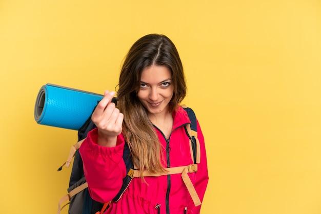 Молодой альпинист с большим рюкзаком на желтом фоне делает денежный жест