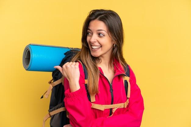 製品を提示する側を指している黄色の背景に分離された大きなバックパックを持つ若い登山家の男