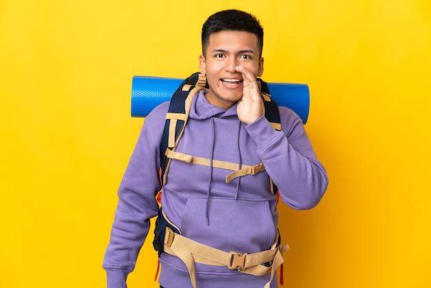 Молодой альпинист с большим рюкзаком на желтом фоне кричит с широко открытым ртом