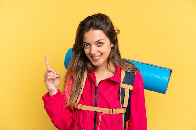 Молодой альпинист с большим рюкзаком на желтом фоне показывает и поднимает палец в знак лучших