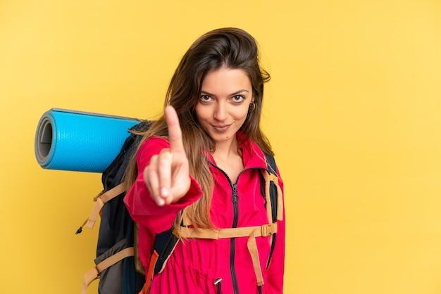 Молодой альпинист с большим рюкзаком на желтом фоне показывает и поднимает палец