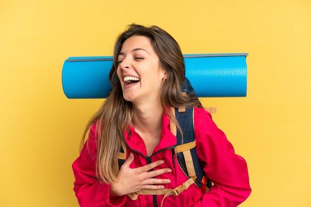 Молодой альпинист с большим рюкзаком на желтом фоне много улыбается