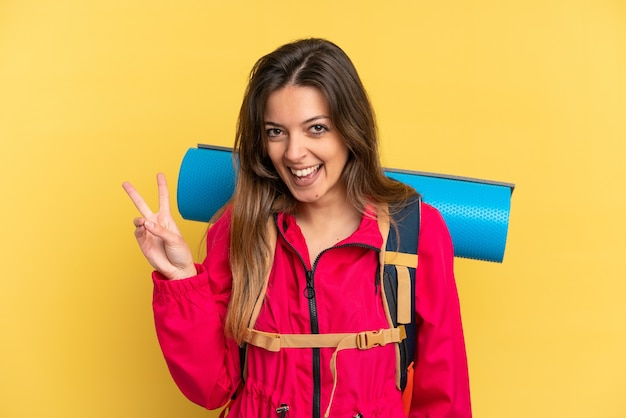 Молодой альпинист с большим рюкзаком на желтом фоне улыбается и показывает знак победы