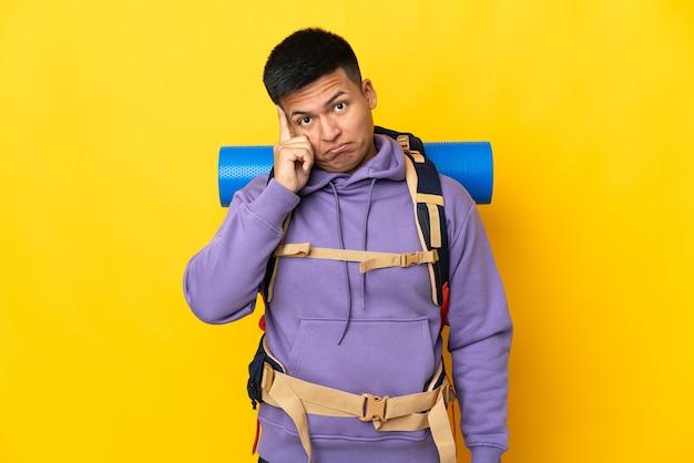 Молодой альпинист с большим рюкзаком на желтом фоне думает об идее