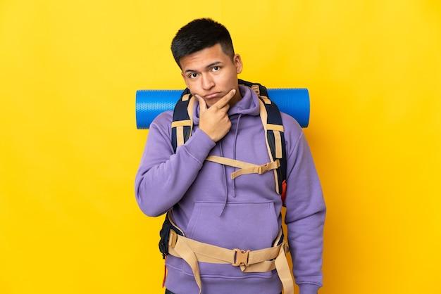黄色の背景思考に分離された大きなバックパックを持つ若い登山家の男