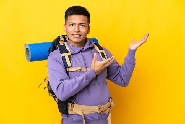 노란색 벽에 고립 된 큰 배낭을 가진 젊은 산악인 남자가 와서 초대하기 위해 손을 옆으로 확장