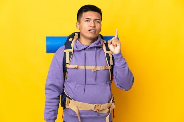 손가락을 들어 올리는 동안 해결책을 실현하려는 노란색 벽에 고립 된 큰 배낭을 가진 젊은 등산가 남자