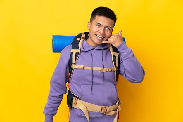 Молодой альпинист с большим рюкзаком, изолированным на желтой стене, делая телефонный жест. перезвони мне знак