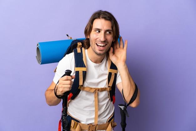 耳に手を置いて何かを聞いている大きなバックパックを持つ若い登山家の男