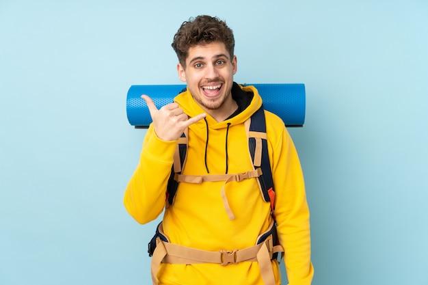 電話ジェスチャーを作る青い壁に大きなバックパックを持つ若い登山家男
