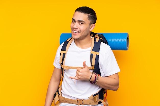 電話ジェスチャーを作る黄色の大きなバックパックを持つ若い登山家男