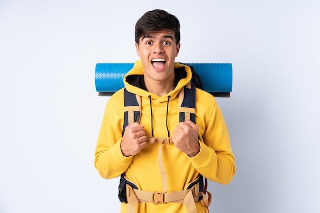 勝利を祝っている青い壁に大きなバックパックを持つ若い登山家男