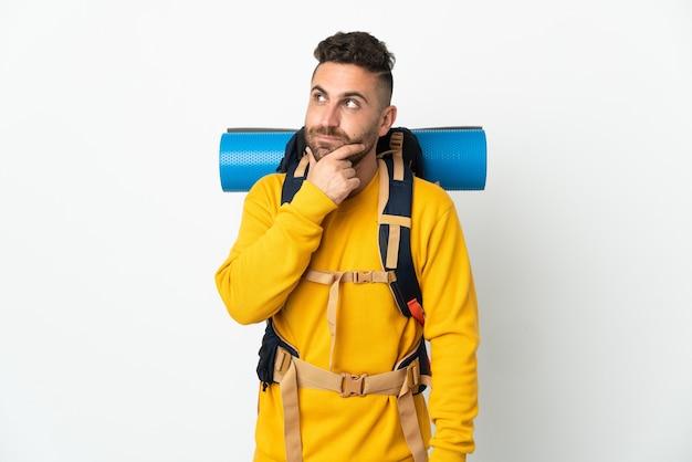 孤立して見上げる大きなバックパックを持つ若い登山家の男