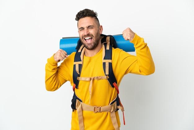 Молодой альпинист с большим рюкзаком на изолированном фоне празднует победу