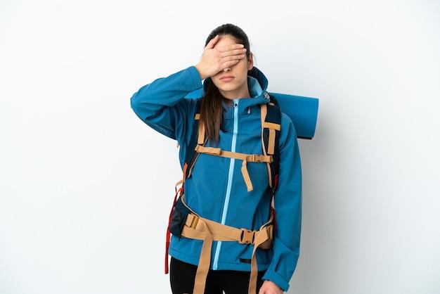 手で目を覆っている孤立した背景の上に大きなバックパックを持つ若い登山家の男。何かを見たくない