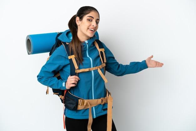Молодой альпинист с большим рюкзаком на изолированном фоне, протягивая руки в сторону, приглашая приехать