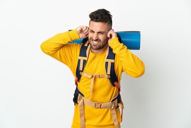 Молодой альпинист с большим рюкзаком на изолированном фоне разочарован и закрывает уши