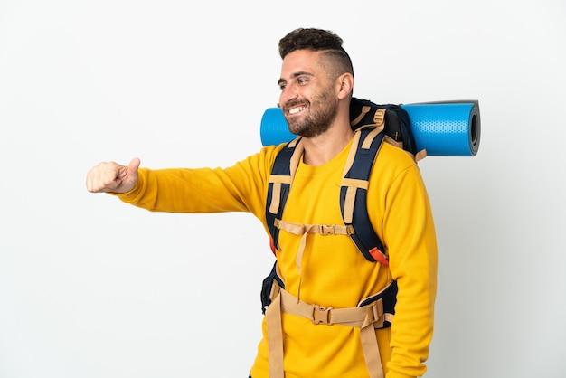 親指を立てるジェスチャーを与える孤立した背景の上に大きなバックパックを持つ若い登山家の男