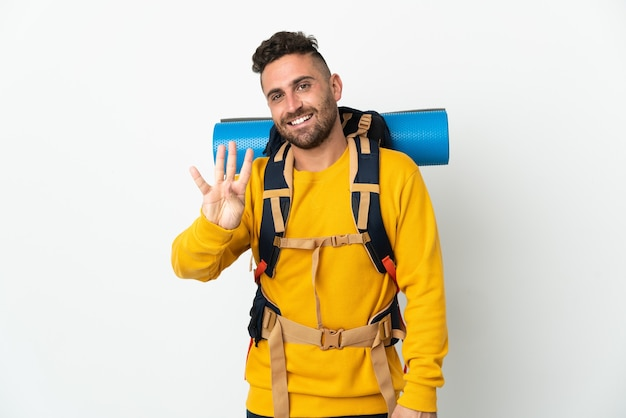 Молодой альпинист с большим рюкзаком на изолированном фоне счастлив и считает четыре пальцами