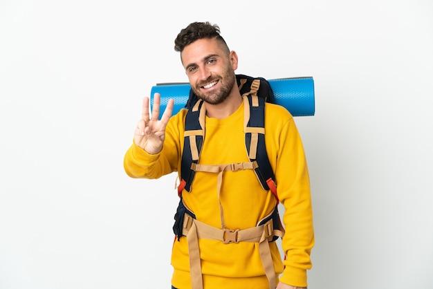Молодой альпинист с большим рюкзаком на изолированном фоне счастлив и считает три пальцами