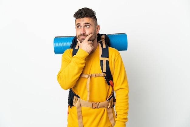Молодой альпинист с большим рюкзаком на изолированном фоне сомневается