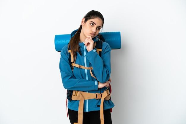 Молодой альпинист с большим рюкзаком на изолированном фоне, сомневаясь