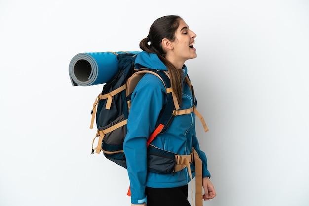Молодой альпинист с большим рюкзаком на изолированном фоне смеется в боковом положении