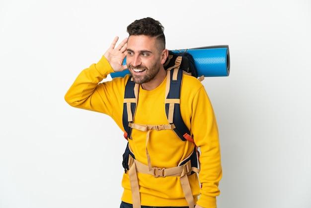 Молодой альпинист с большим рюкзаком на изолированном фоне слушает что-то, положив руку на ухо