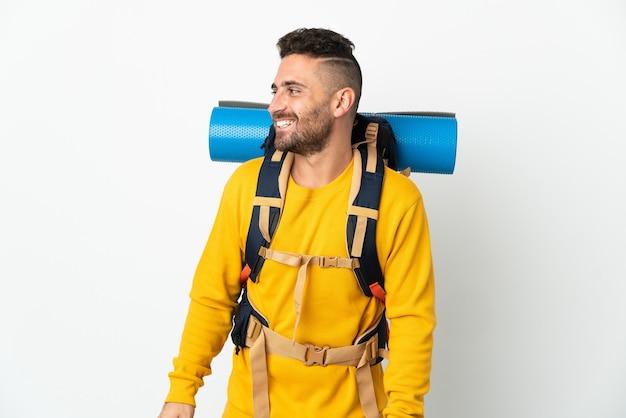Молодой альпинист с большим рюкзаком на изолированном фоне, глядя в сторону и улыбаясь