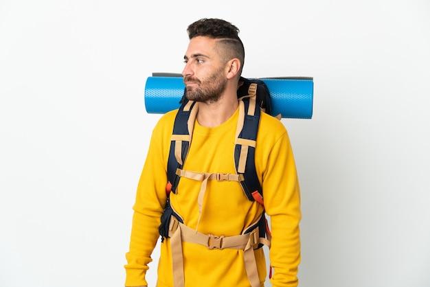 Молодой альпинист с большим рюкзаком на изолированном фоне, глядя в сторону
