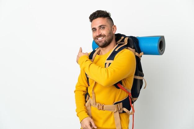 Молодой альпинист с большим рюкзаком на изолированном фоне, указывая назад