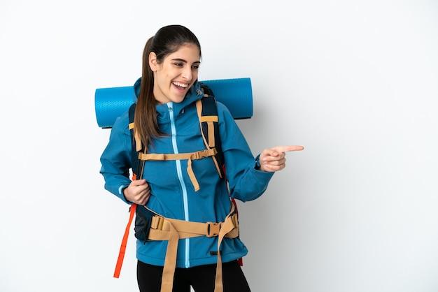横に指を指し、製品を提示する孤立した背景の上に大きなバックパックを持つ若い登山家の男