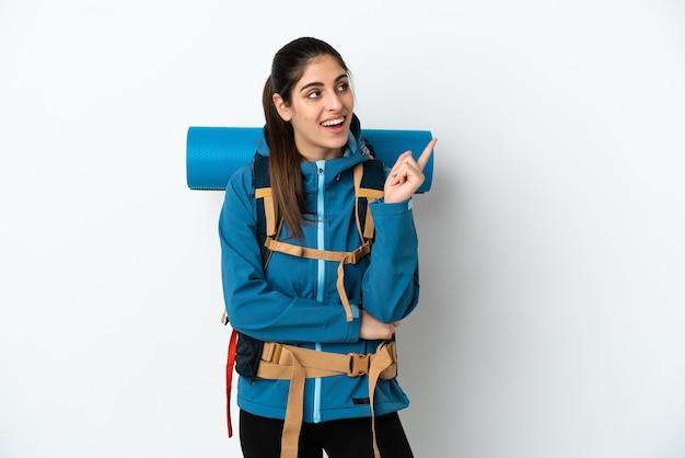 素晴らしいアイデアを指している孤立した背景の上に大きなバックパックを持つ若い登山家の男