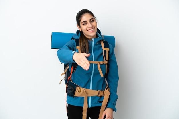 Молодой альпинист с большим рюкзаком на изолированном фоне, пожимая руку для заключения хорошей сделки