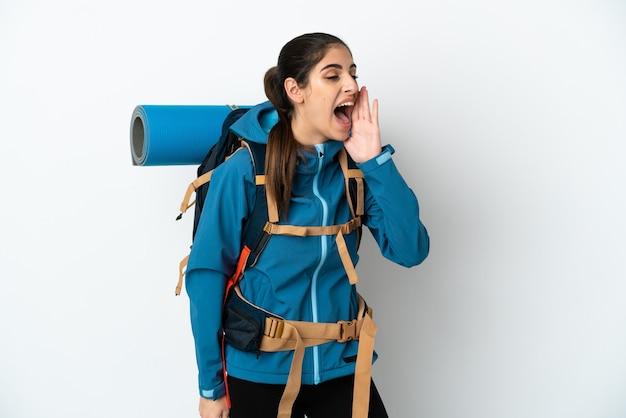 横に大きく開いた口で叫んで孤立した背景の上に大きなバックパックを持つ若い登山家の男