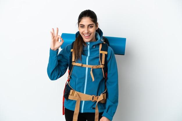 指でokサインを示す孤立した背景の上に大きなバックパックを持つ若い登山家の男