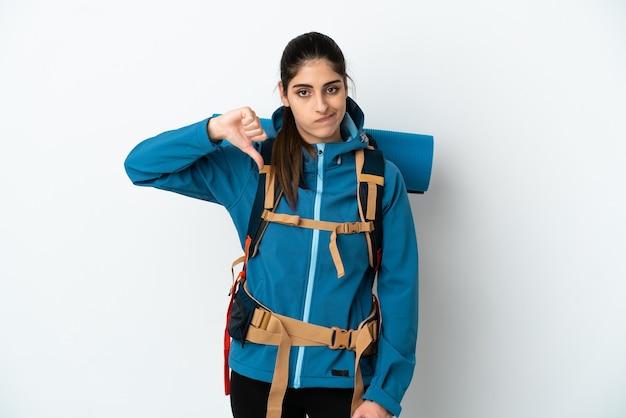 Молодой альпинист с большим рюкзаком на изолированном фоне показывает большой палец вниз с отрицательным выражением лица