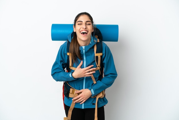 Молодой альпинист с большим рюкзаком на изолированном фоне много улыбается